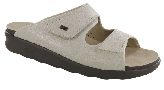 """A thick-soled cream colored open heeled sandal with velcro straps and a """"SAS"""" insignia"""