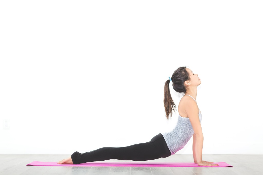 A woman on a pink mat with a white background extending her body into the cobra yoga position - shoulders back, head tilted upward, feet pointing downward, hips and legs hovering above the mat.